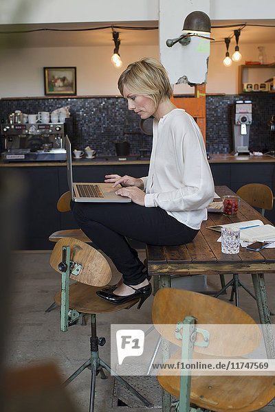 Mid adult woman sitting on table using laptop
