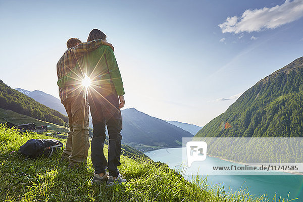 Young couple looking out over Vernagt reservoir and Finailhof farmhouse  Val Senales  South Tyrol  Italy