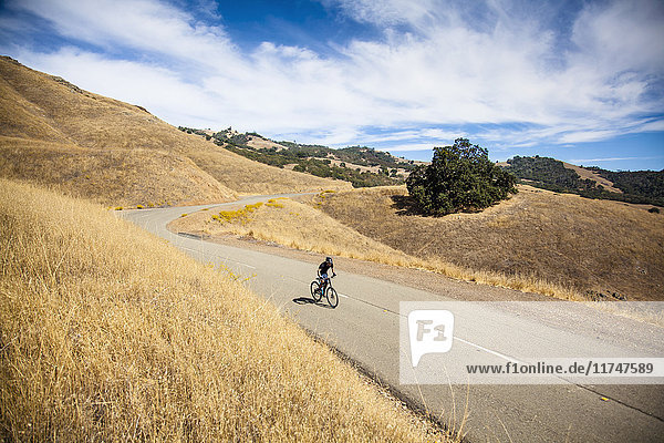 Elevated view of young man mountain biking up rural road  Mount Diablo  Bay Area  California  USA