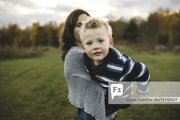 Mother holding son  leaning forward looking at camera smiling