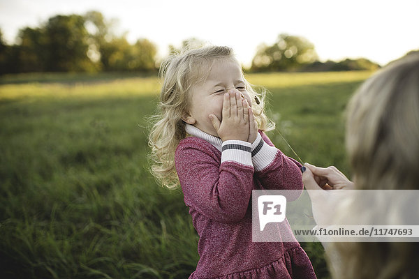 Mid adult woman tickling daughters face with stem of grass in field