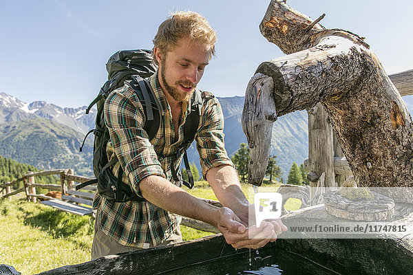 Young male hiker drinking water from rustic trough  Karthaus  Val Senales  South Tyrol  Italy