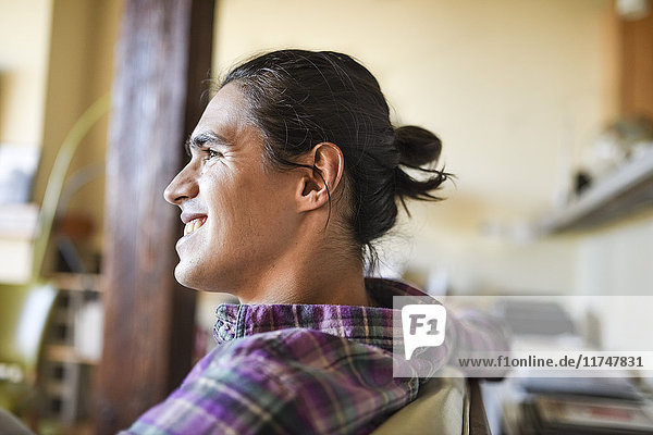 Young man sitting indoors relaxing  smiling