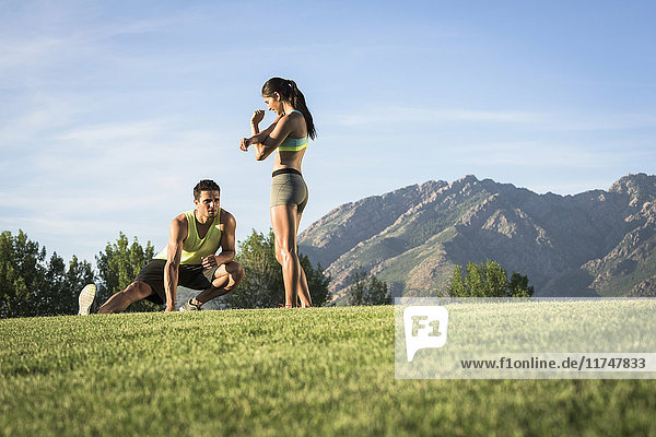 Junger Mann und Frau beim Aufwärmtraining im Park