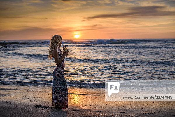 Junge Frau trinkt Cocktail am Strand bei Sonnenuntergang  Tamarindo  Costa Rica