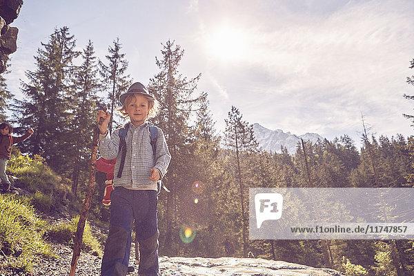 Bildnis eines Jungen auf einem Felsen stehend  im Wald