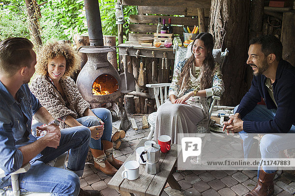 Vier erwachsene Freunde trinken Kaffee in einer offenen Hütte mit Holzofen