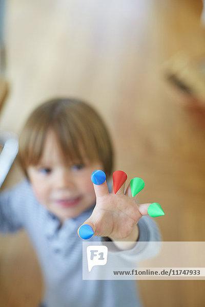 Nahaufnahme einer Jungenhand mit bunten Zapfen an den Fingern
