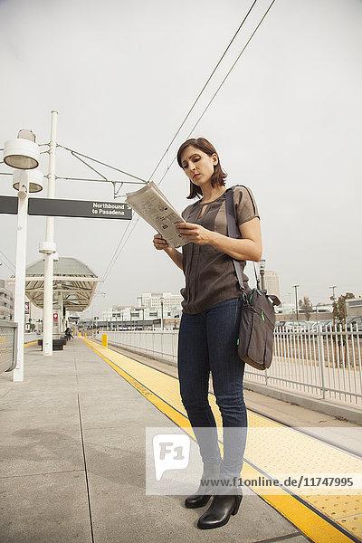 Frau liest Zeitung  während sie am Bahnhof wartet  Los Angeles  Kalifornien  USA