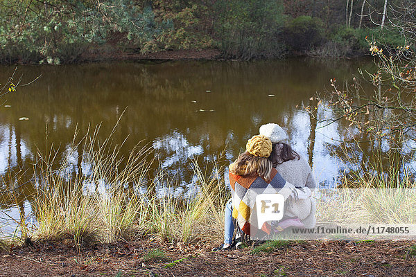 Rear view of teenage girl sitting on river bank side by side hugging