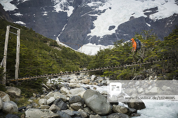 Mann überquert Brücke über den Rio del Frances  Torres del Paine Nationalpark  Chile