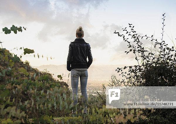 Mittelgroße erwachsene Frau beim Betrachten der Aussicht auf dem Land