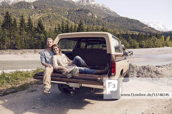 Paar sitzt hinten auf einem Pickup und schaut in die Kamera  Wallgau  Bayern  Deutschland