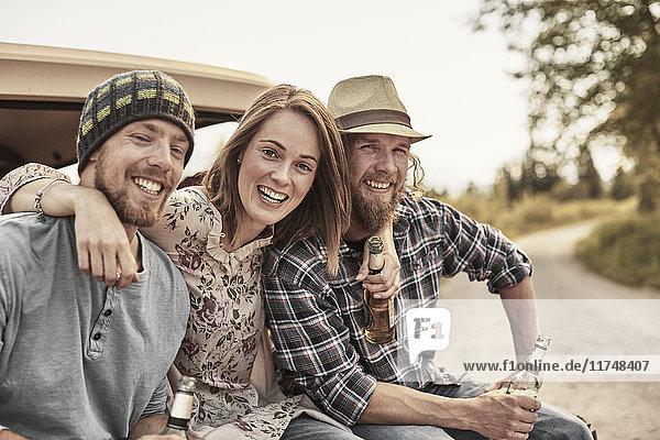 Drei Personen  die Bierflaschen halten  in die Kamera schauen und lächeln