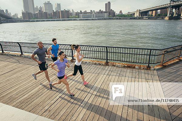 Four adult runners running along riverside  Brooklyn  New York  USA