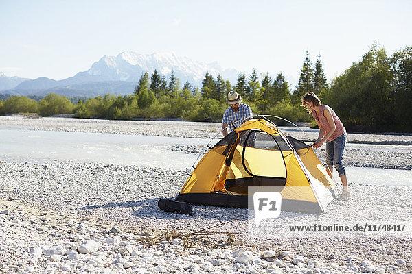 Ehepaar errichtet gelbes Zelt am Wasser  Wallgau  Bayern  Deutschland