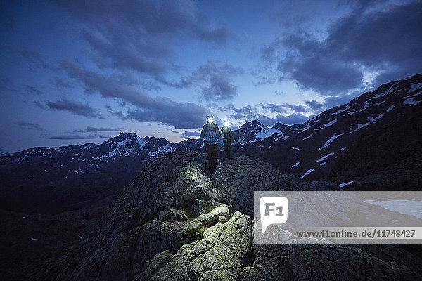 Young couple hiking at night wearing headlamps  Val Senales Glacier  Val Senales  South Tyrol  Italy