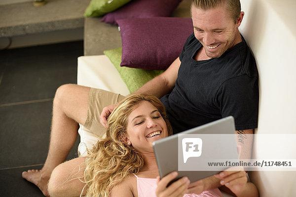 Auf dem Sofa liegendes Paar stöbert auf digitalem Tablett