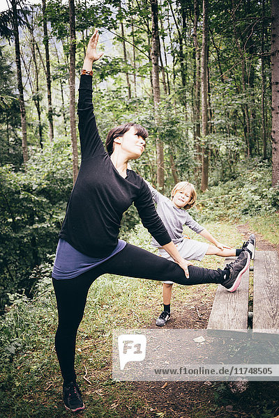 Mother and son in forest legs raised on picnic table stretching  Bludenz  Vorarlberg  Austria