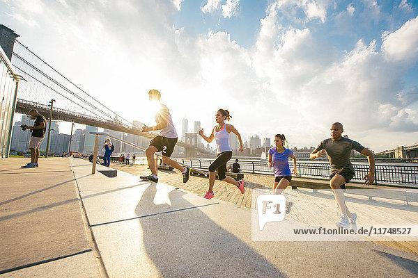 Four running friends running up riverside stairs  New York  USA