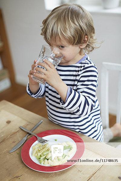Junge trinkt Wasser am Esstisch