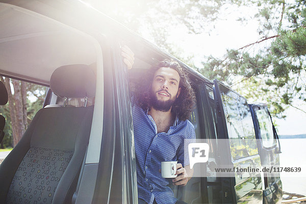 Young man having coffee in van by lake