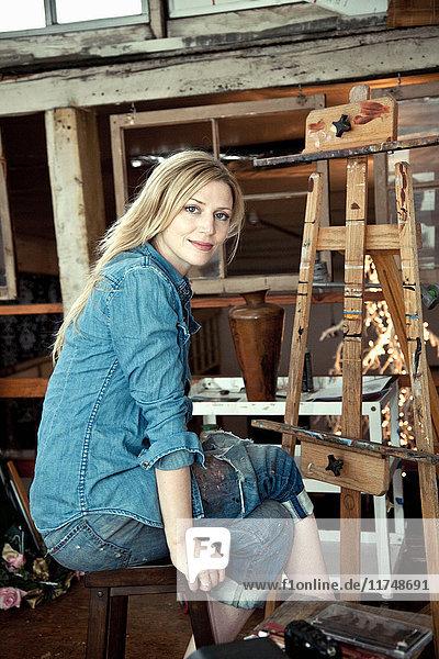Mittlere erwachsene Frau im Atelier des Künstlers sitzend  Porträt