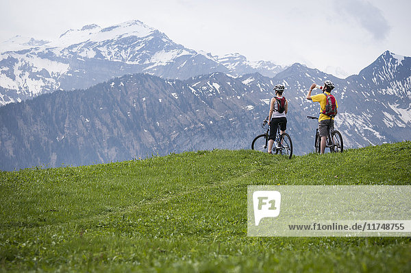 Couple mountain biking in Swiss Alps  near Waldegg  Bernese Oberland  Switzerland