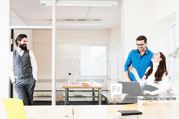 Kollegen im Büro  lachende Frau mit Laptop