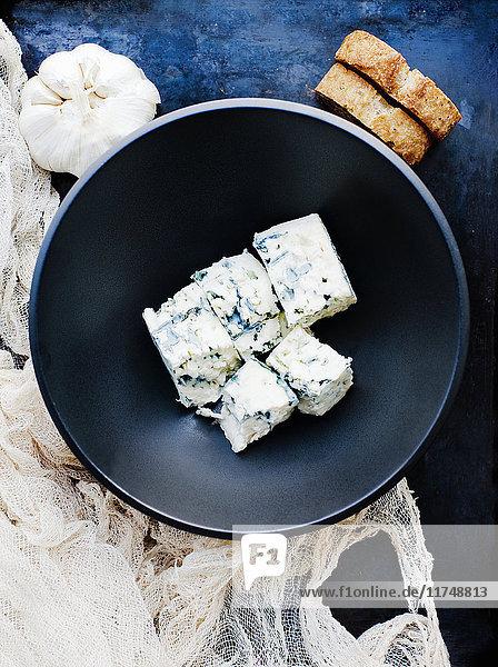 Knoblauchzwiebel und Schale mit gewürfeltem Blauschimmelkäse