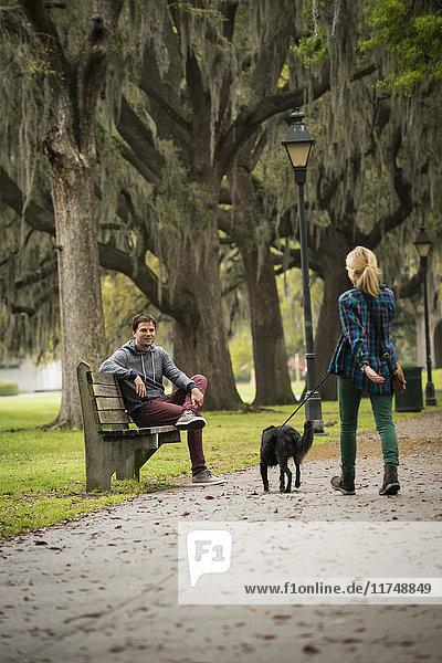 Man on park bench  woman walking dog  Savannah  Georgia  USA