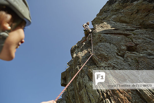 Low angle view of young rock climbing couple climbing rock formation  Val Senales  South Tyrol  Italy