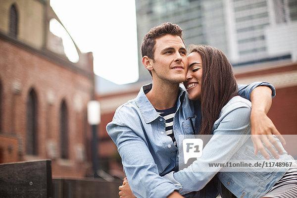 Junges Paar umarmt sich in der Stadt und lächelt