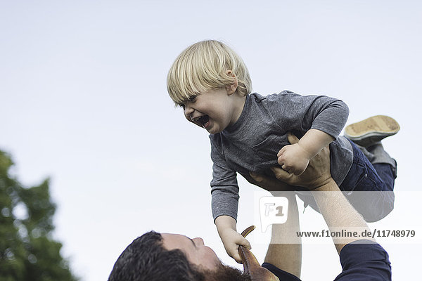 Father holding son in air  outdoors