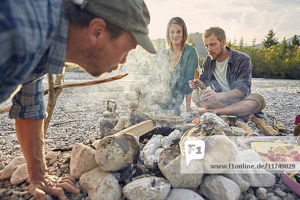 Erwachsene  die am Lagerfeuer sitzen  Essen zubereiten und Glut blasen