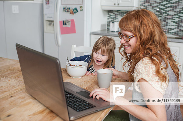 Mother and daughter having breakfast and using laptop