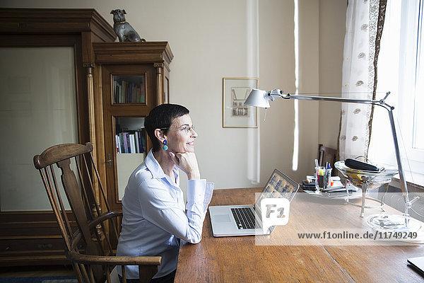 Frau sitzt am Schreibtisch vor dem Laptop
