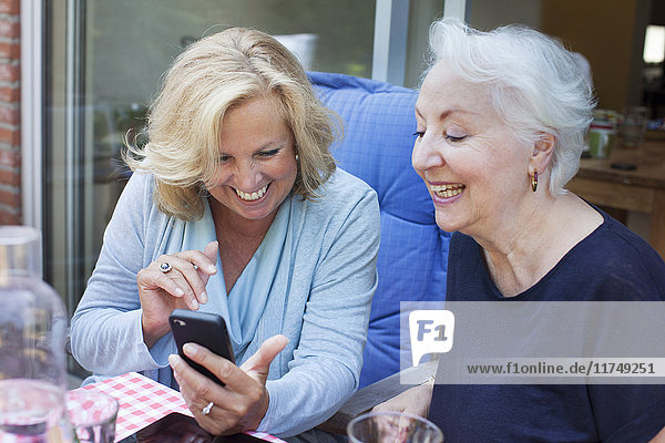 Two women  sitting outdoors  looking at smartphone