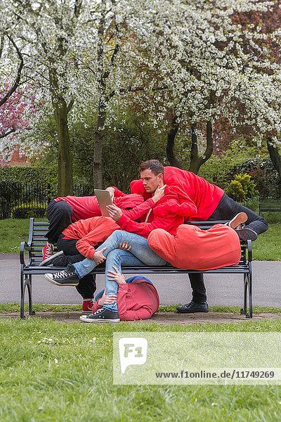 Gruppe junger Leute  die auf der Parkbank der Stadt auftreten
