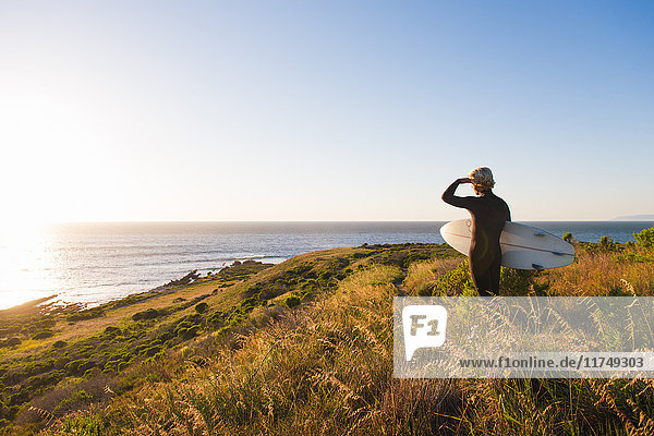 Rückansicht eines jungen männlichen Surfers  der von einer Klippe auf das Meer schaut