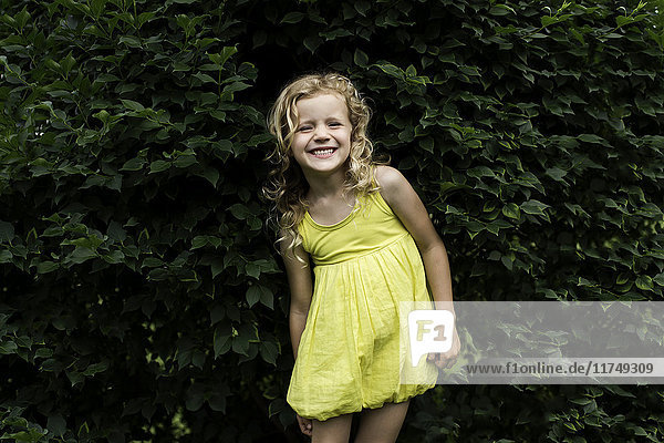 Portrait of smiling blond haired girl wearing yellow dress standing in front of garden hedge