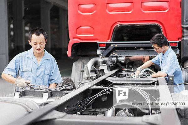 Zwei männliche Fabrikarbeiter bei der Teamarbeit auf einem Lastwagen in einer Kranfabrik  China