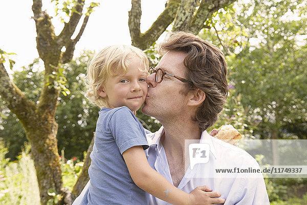 Porträt eines reifen Mannes  der seinen Sohn im Garten auf die Wange küsst