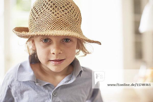 Porträt eines Jungen mit Strohhut  der in die Kamera schaut