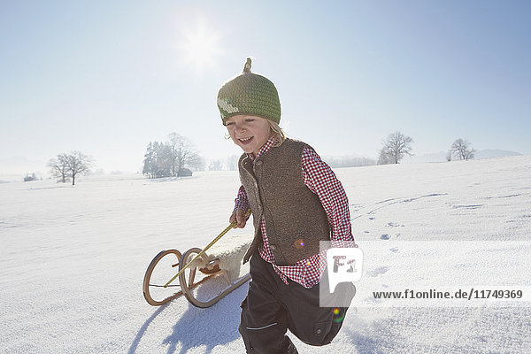 Junge rennt  zieht Schlitten