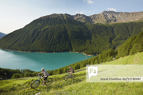 Young couple mountain biking at Vernagt reservoir  Val Senales  South Tyrol  Italy