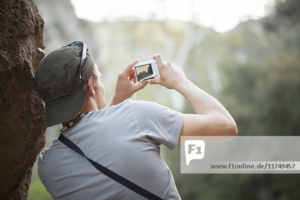 Young man next to rock taking photograph on digital camera