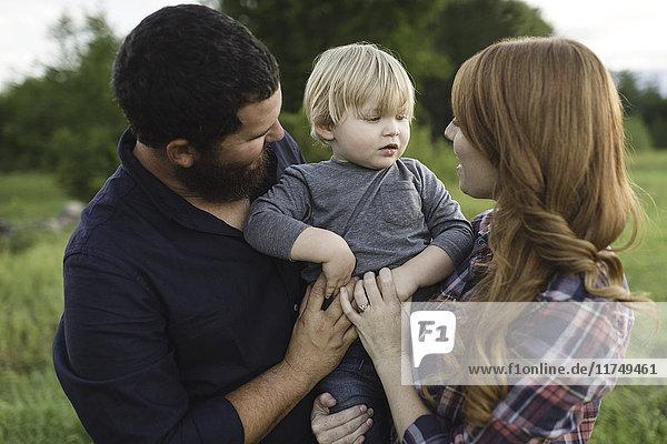 Mutter und Vater halten einen kleinen Sohn im Freien