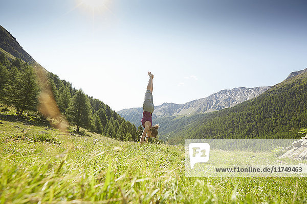 Young woman doing handstand  Val Senales  South Tyrol  Italy