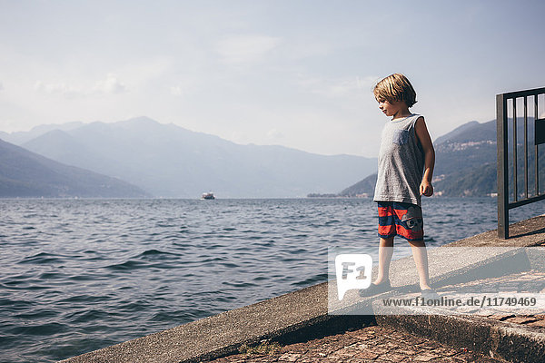 Boy standing on slope by water looking away  Luino  Lombardy  Italy